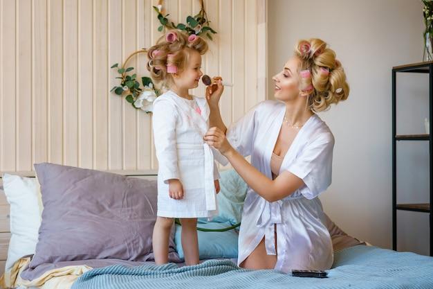 Mãe e filha em bobes, fazer um make-up para o outro, uma família feliz