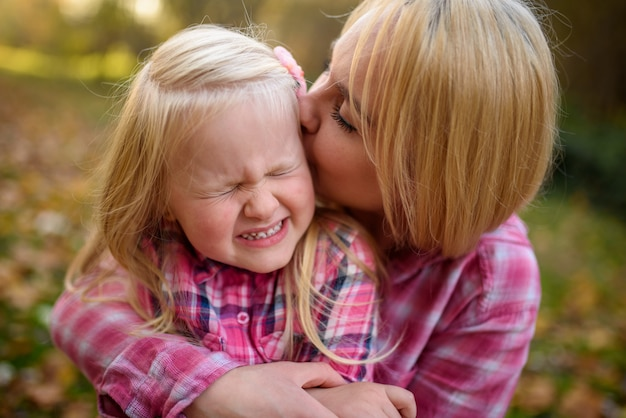 Mãe e filha em camisas cor de rosa. mulher beija uma garota.