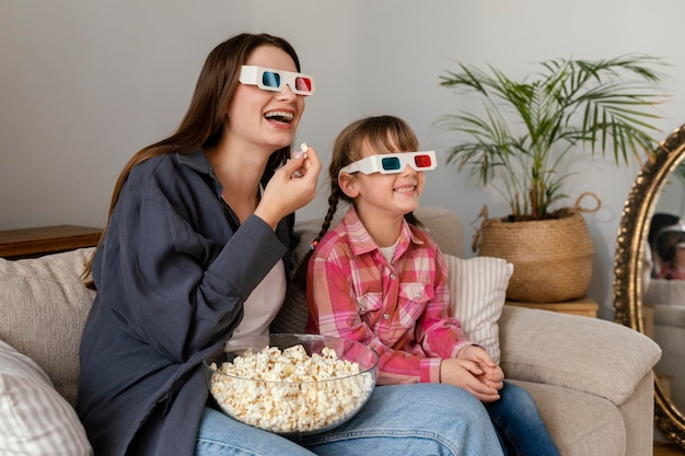 Mãe e filha em casa assistindo filme