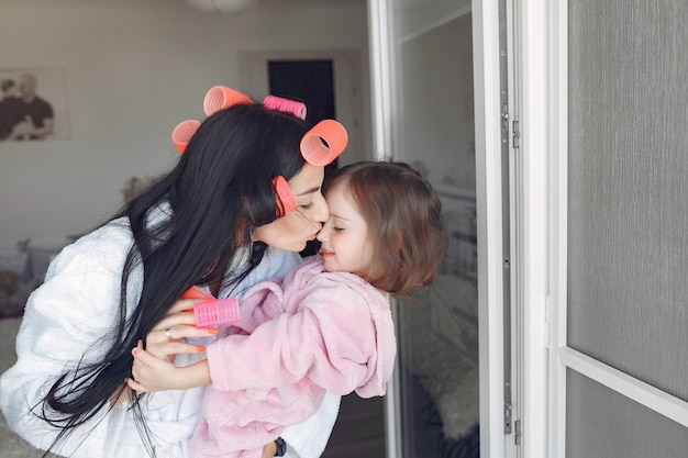 Mãe e filha em casa com rolinhos na cabeça