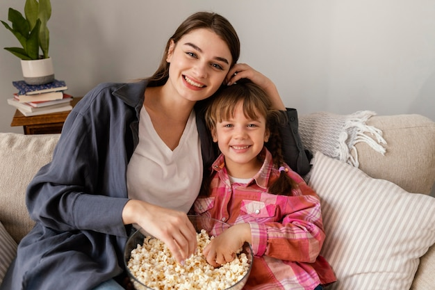 Mãe e filha em casa comendo pipoca