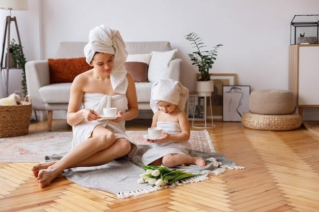 Mãe e filha em casa em toalhas bebem chá após o banho
