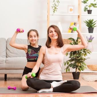 Mãe e filha em casa malhando