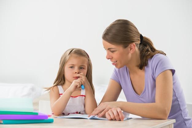 Mãe e filha em casa. mamãe ensina garota a desenhar e a escrever