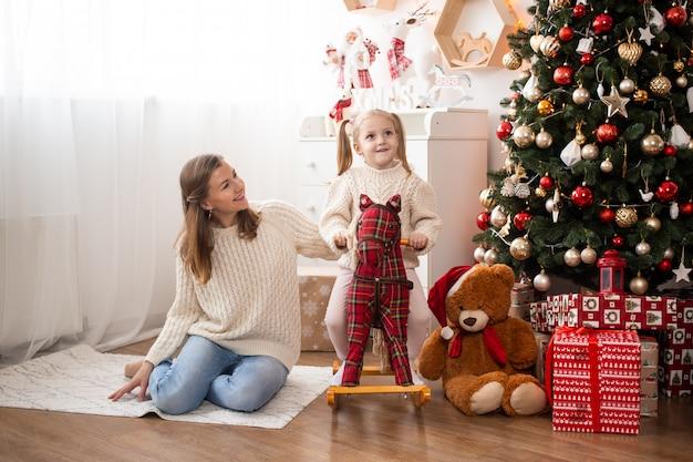 Mãe e filha em casa perto de árvore de natal e caixas de presente