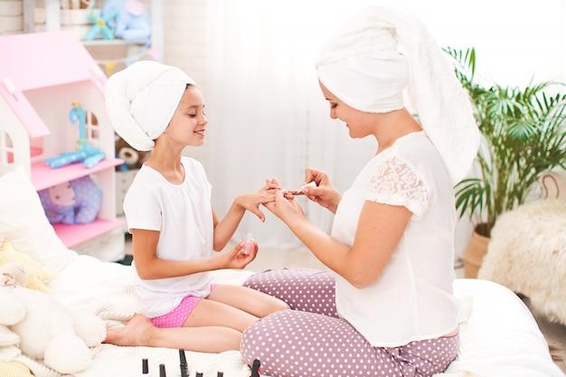 Mãe e filha em casa roupas e toalhas na cabeça fazem manicure