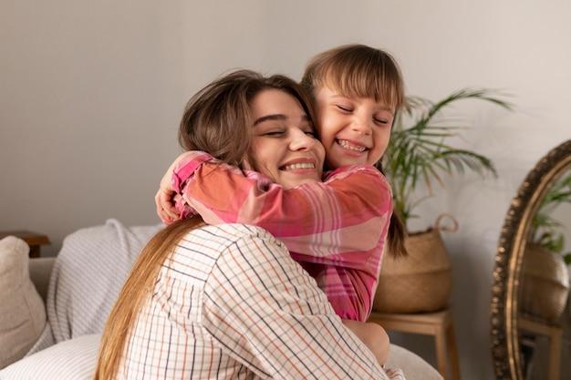 Mãe e filha em casa se abraçando