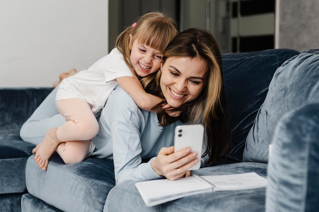 Mãe e filha em casa tirando uma foto de si mesma