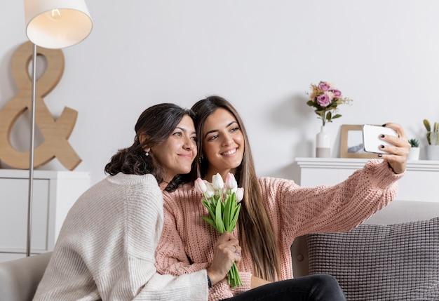 Mãe e filha em casa tomando selfie