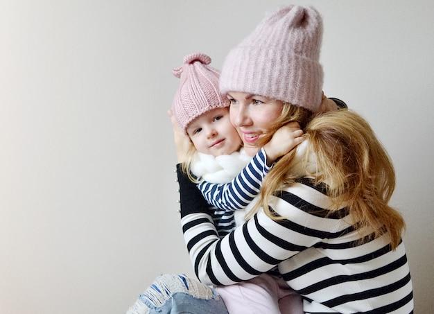 Mãe e filha em chapéus e cachecol em um fundo branco, olhar de família