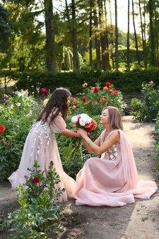Mãe e filha em longos tons pastel e vestidos idênticos no jardim com geórgonas. filha dá flores para a mãe.