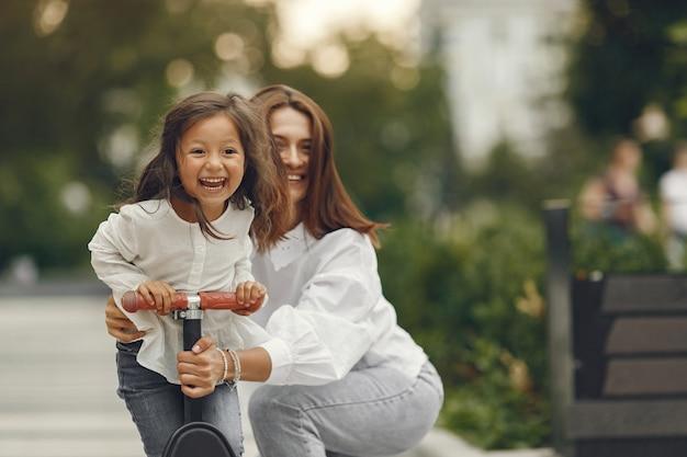 Mãe e filha em patinete no parque. as crianças aprendem a patinar. menina patinando num dia ensolarado de verão.