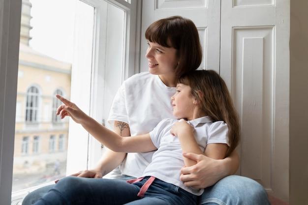 Mãe e filha em plano médio olhando pela janela