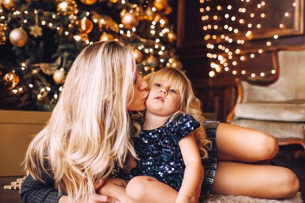 Mãe e filha em roupas brilhantes, abraçando e sorrindo, noite de inverno juntos em casa em uma sala de estar decorada na véspera de natal.