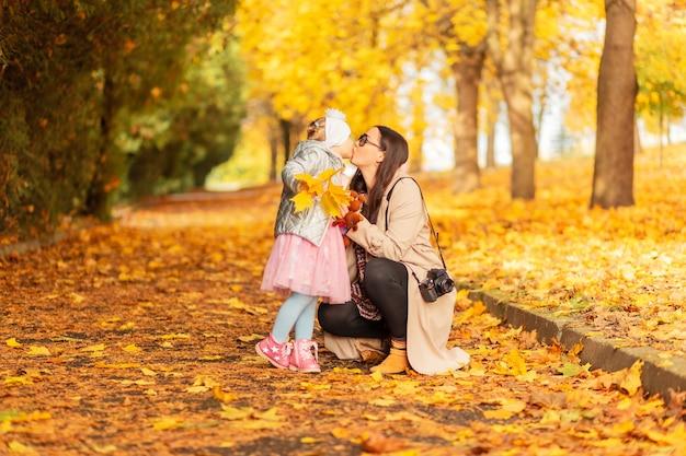 Mãe e filha em roupas da moda caminham no parque e fazem um beijo no fundo da folhagem amarela de outono
