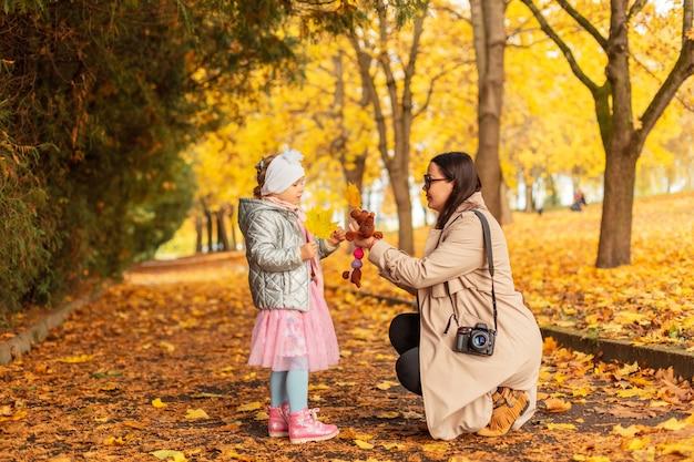 Mãe e filha em roupas da moda com uma câmera estão caminhando em um parque de outono com folhagem amarela brilhante