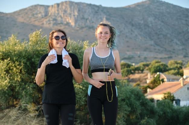 Mãe e filha em roupas esportivas fazendo exercícios juntos