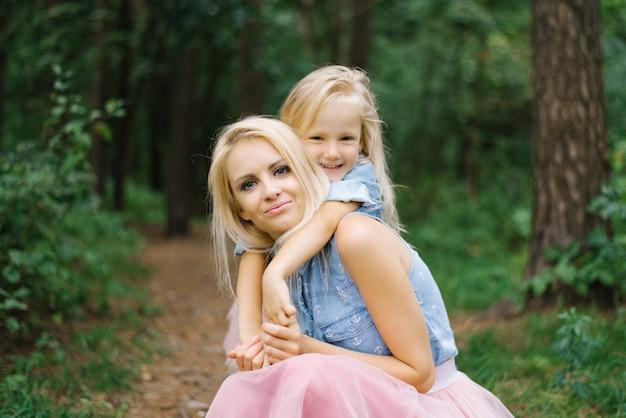 Mãe e filha em saias de tule rosa idênticas e camisas jeans azuis