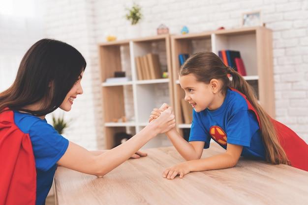 Mãe e filha em ternos de super-heróis.