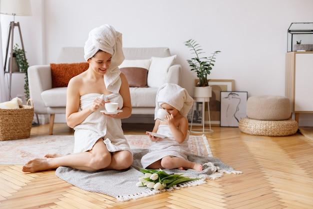 Mãe e filha em toalhas passam um tempo juntas