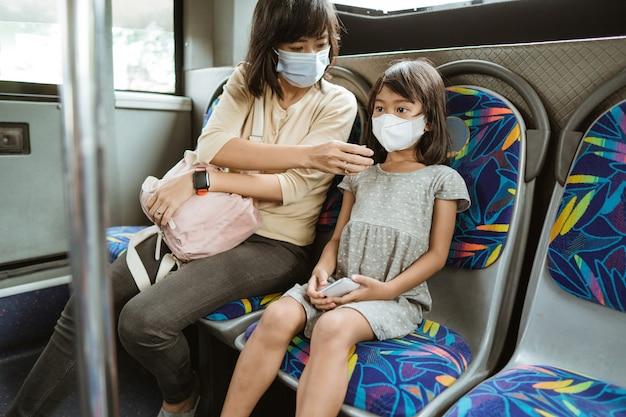 Mãe e filha em transporte público durante pandemia usando máscara