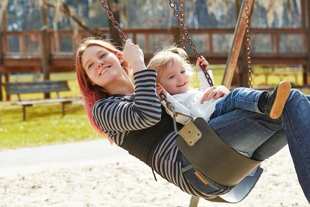 Mãe e filha em um balanço no parque