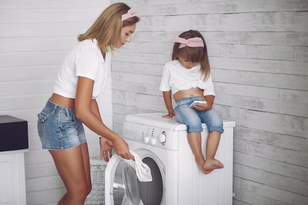 Mãe e filha em um banheiro perto de lavagem mashine