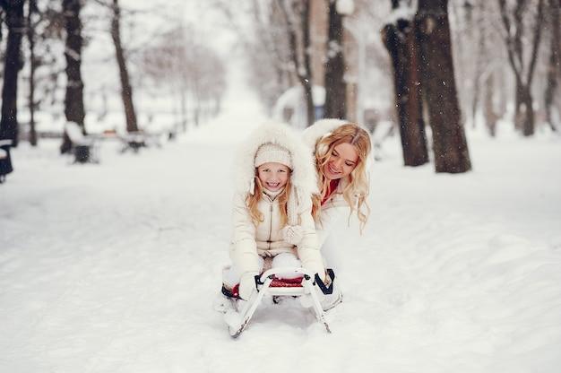 Mãe e filha em um parque de inverno