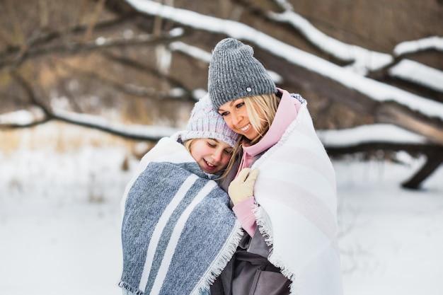 Mãe e filha em um passeio de inverno, envolto em um cobertor, floresta, campo, inverno
