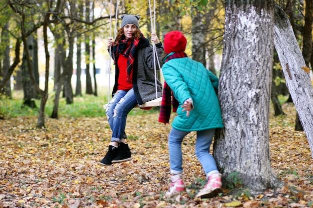 Mãe e filha em um passeio no parque de outono durante o outono