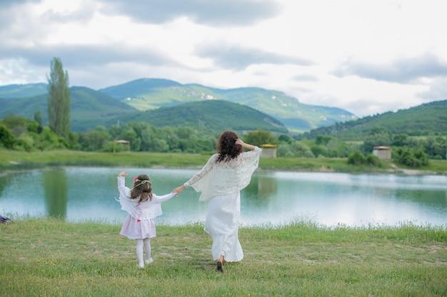 Mãe e filha em um pasto perto de um lago de montanha