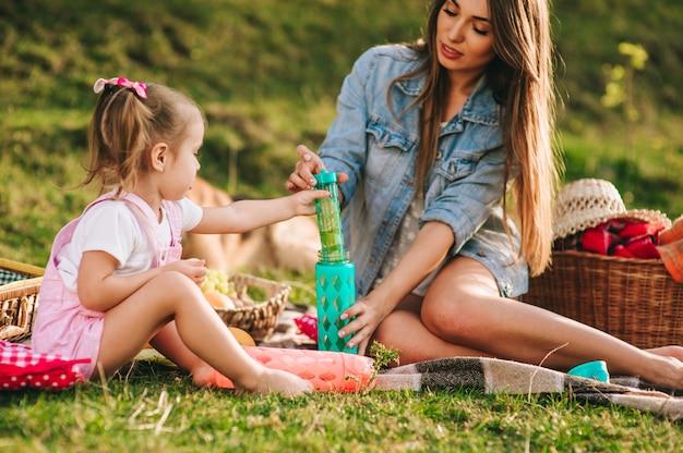Mãe e filha em um piquenique com um cachorro