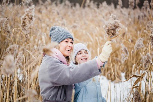 Mãe e filha em uma caminhada na floresta, grama e neve, caminhadas de inverno, floresta, campo, roupas de inverno