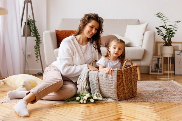 Mãe e filha em uma cesta na sala de estar