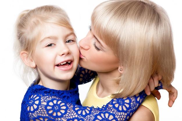 Mãe e filha em vestido colorido sobre fundo branco