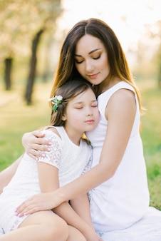 Mãe e filha em vestidos brancos em um piquenique no verão