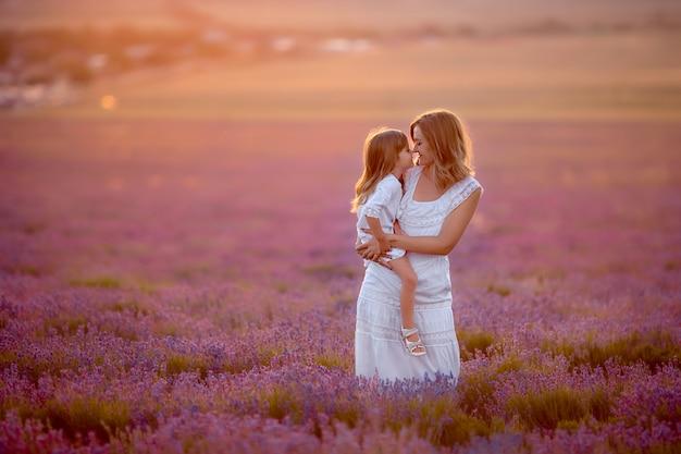 Mãe e filha em vestidos brancos em uma caminhada ao pôr do sol em um campo de lavanda
