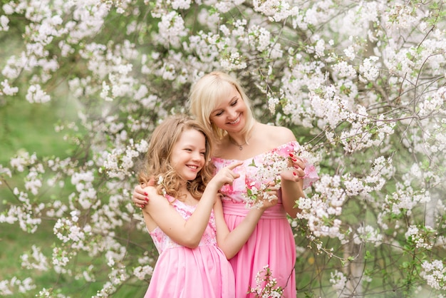 Mãe e filha em vestidos cor de rosa em um jardim florescendo na primavera.