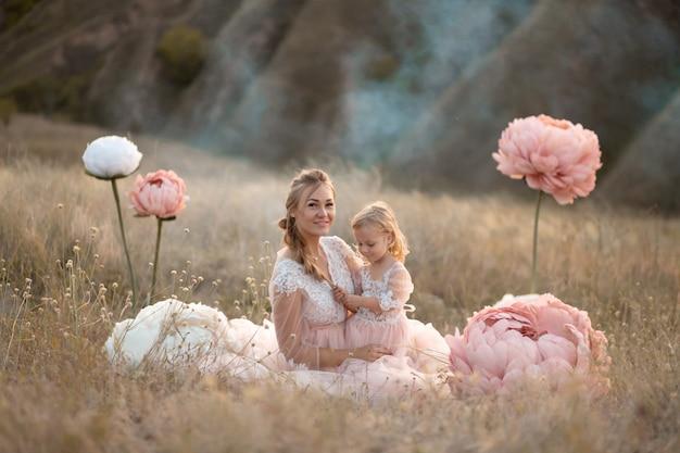 Mãe e filha em vestidos de conto de fadas rosa estão sentados em um campo cercado por grandes flores decorativas rosa