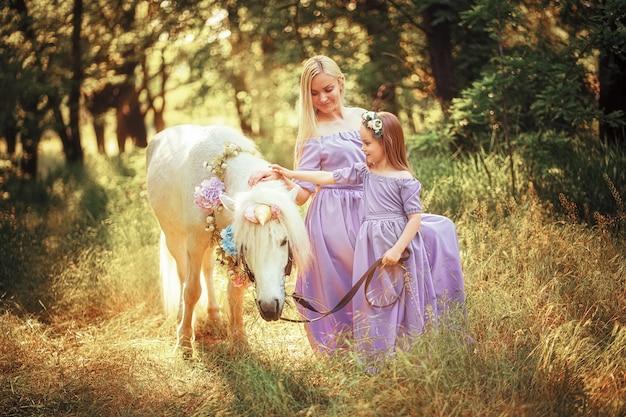 Mãe e filha em vestidos de lavanda semelhantes estão acariciando um cavalo unicórnio. prado de verão
