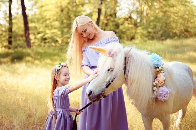 Mãe e filha em vestidos de lavanda semelhantes estão acariciando um unicórnio