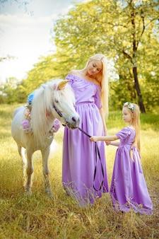 Mãe e filha em vestidos lilás semelhantes estão acariciando uma criança