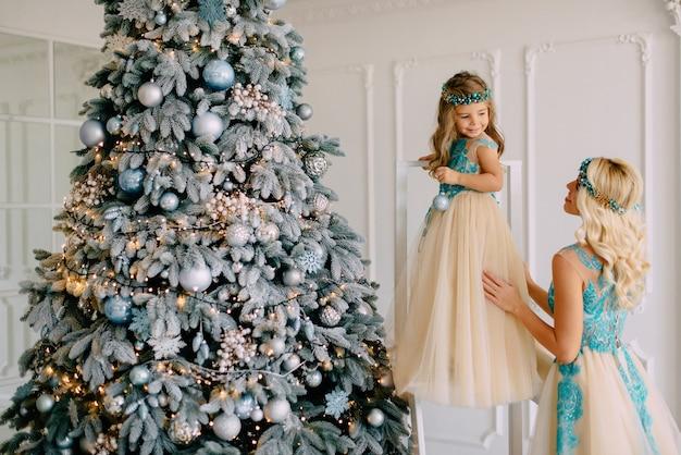 Mãe e filha em vestidos luxuosos decoram a árvore de natal