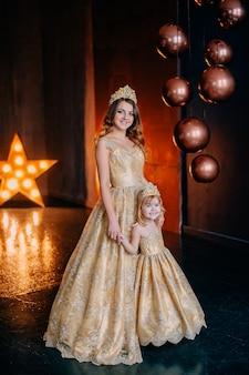 Mãe e filha em vestidos luxuosos no fundo das decorações de ano novo