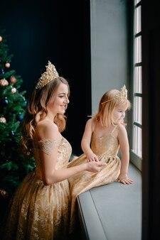 Mãe e filha em vestidos luxuosos perto da árvore de natal, estúdio