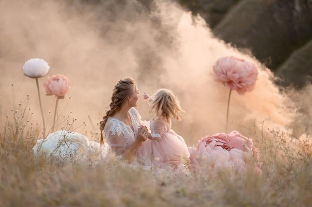 Mãe e filha em vestidos rosa fabulosos olham para longe, sentadas em um campo cercado por grandes flores decorativas rosa