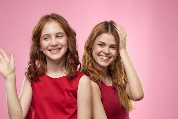 Mãe e filha em vestidos vermelhos abraços diversão careta infância alegria rosa parede.