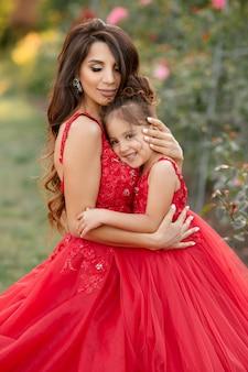 Mãe e filha em vestidos vermelhos andam no jardim de rosas no verão