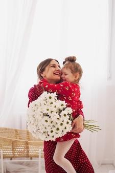 Mãe e filha em vestidos vermelhos em um quarto bem iluminado