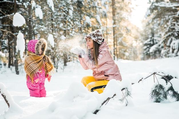 Mãe e filha embrulhada em um lenço em uma floresta de inverno nevado. viagens e recreação